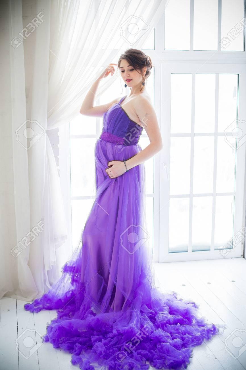 Schöne Schwangere Frau Posiert Im Lila Kleid Im Studio Lizenzfreie ...