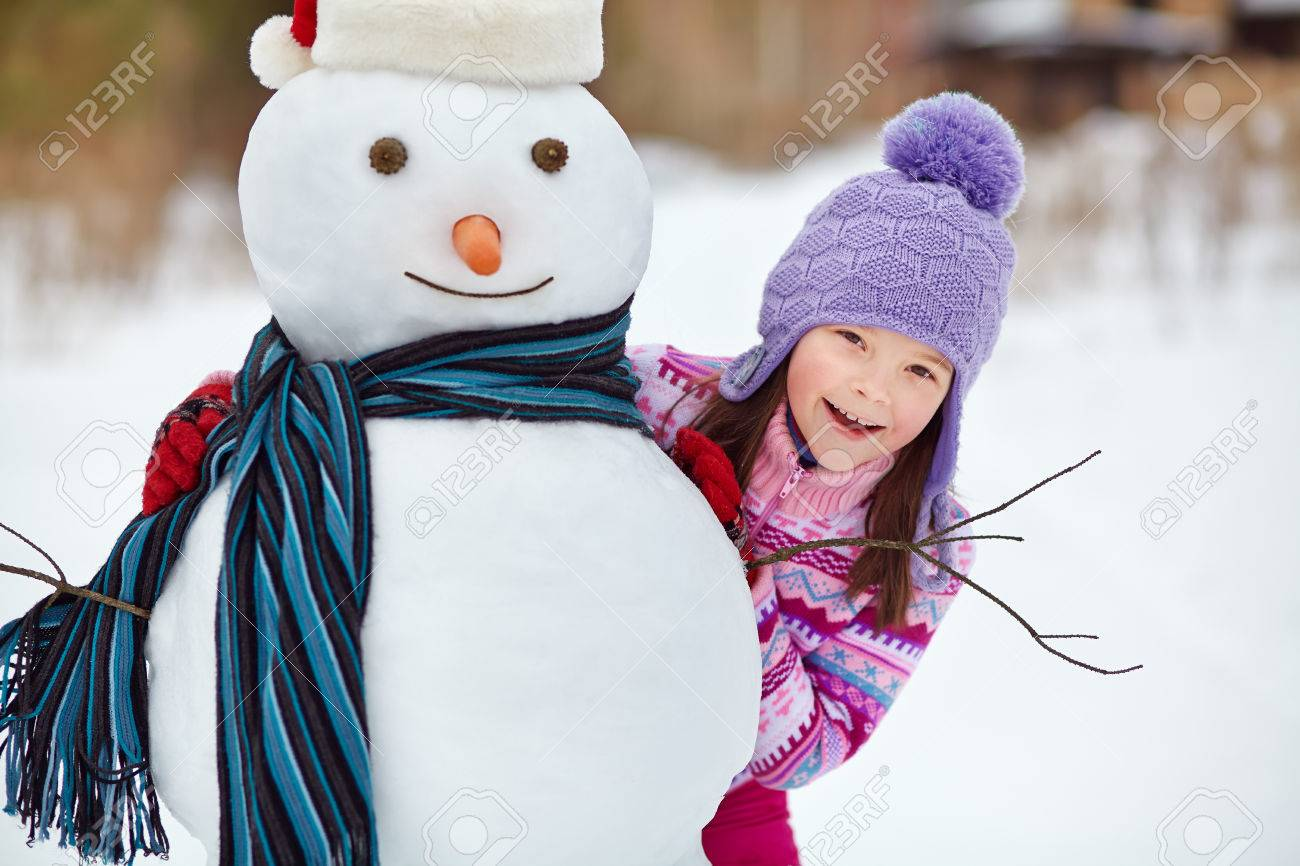 happy kid playing with snowman. funny little girl on a walk in the winter outdoors - 48367272