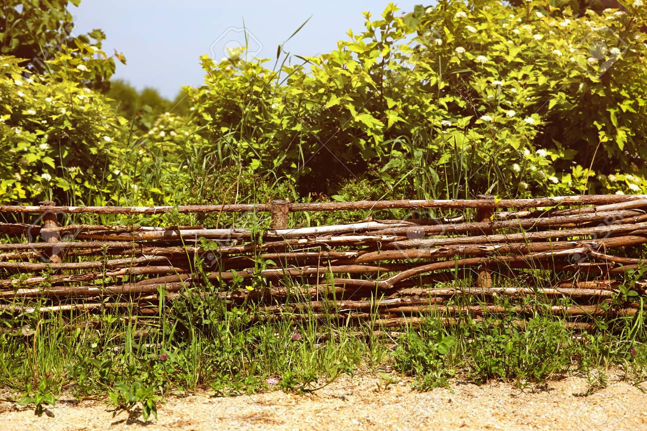 Wicker Rustic Fence In The Summer Garden On Grass Background. Stock ...