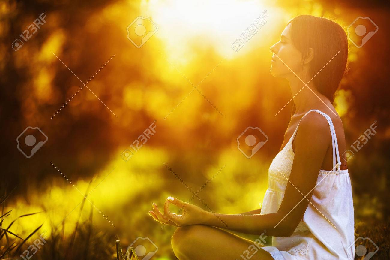 Yoga woman meditating at sunset. Female model meditating in serene harmony Standard-Bild - 43960890