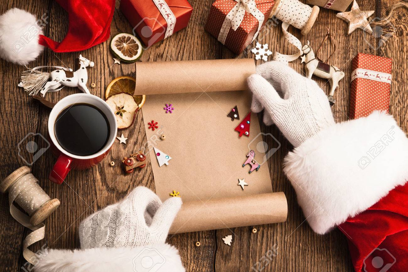 Santa Claus with gifts and wish list on wooden table Standard-Bild - 48841441