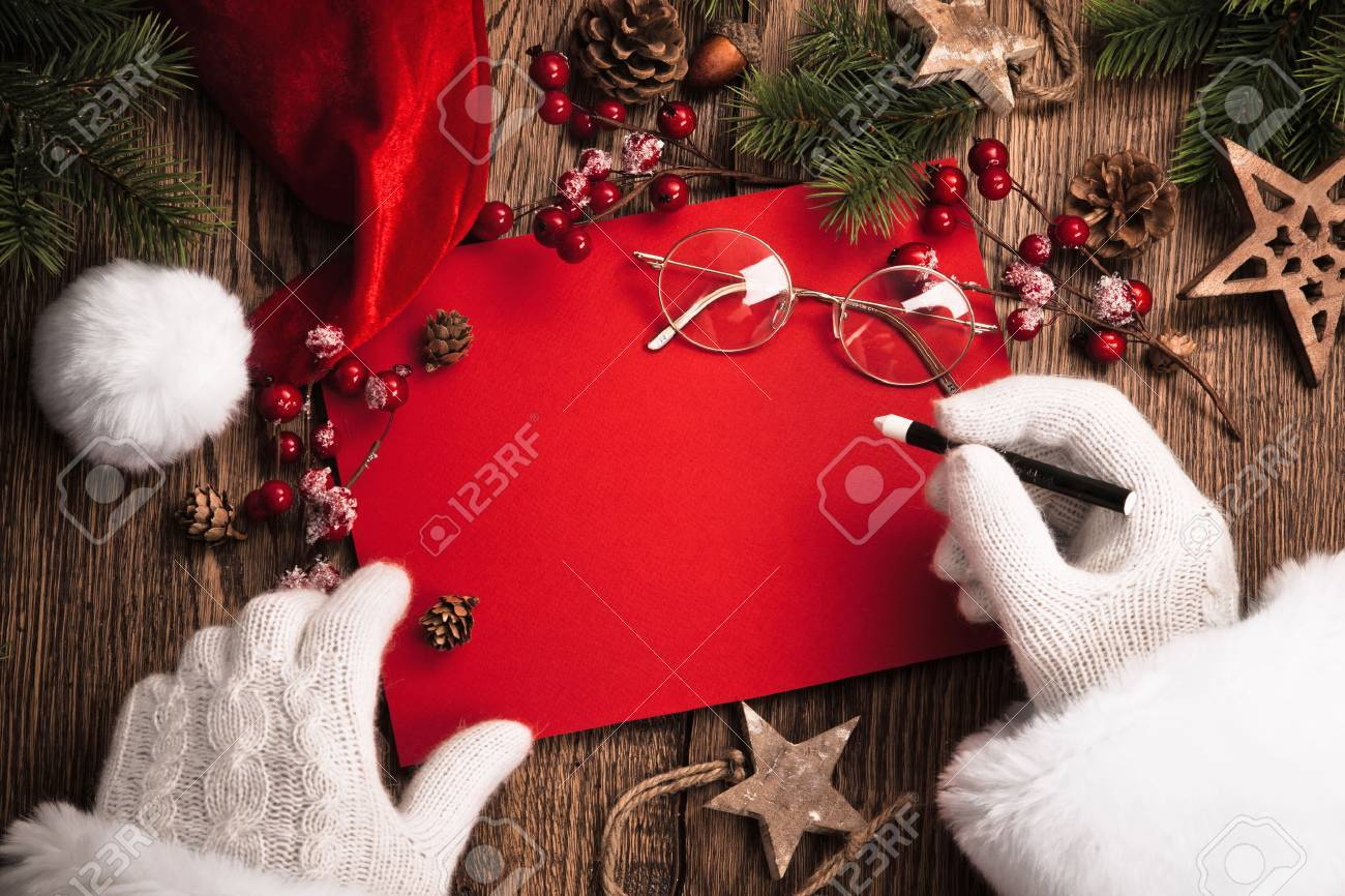 Santa Claus with gifts and red card on wooden table Standard-Bild - 49341746
