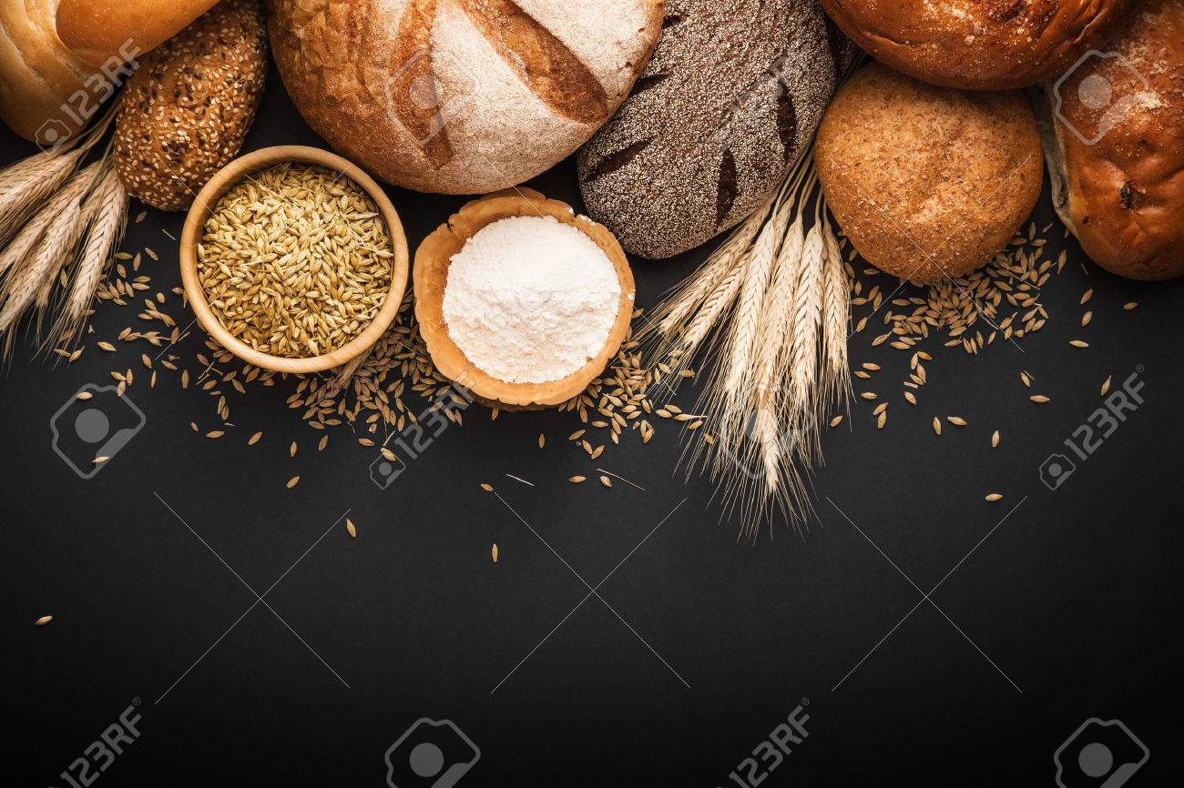 Fresh bread and wheat on black background - 60695661