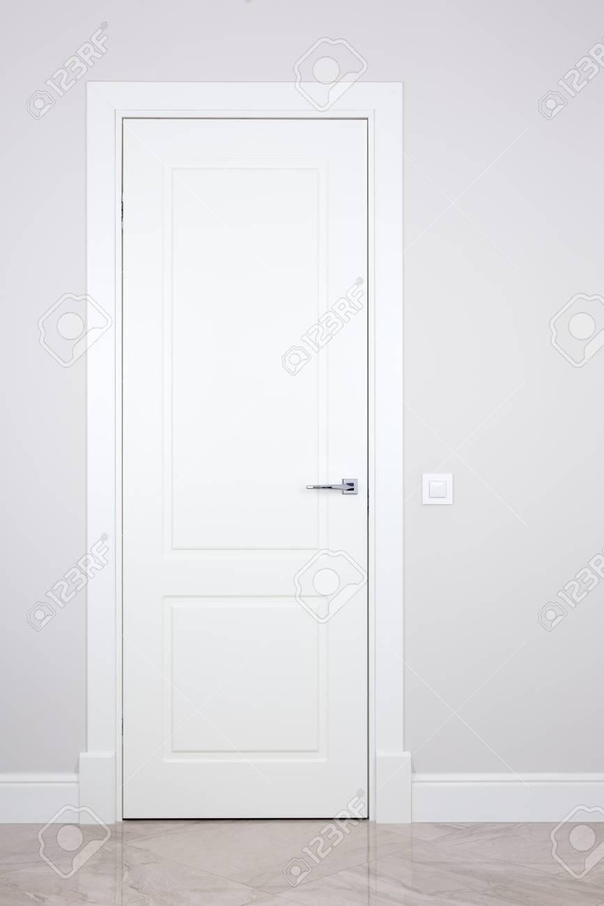 Porte blanche et interrupteur sur un mur gris clair. Articles lumineux  intérieur