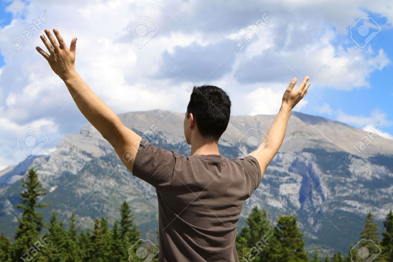 Man standing in nature with arms lifted up - 7483903