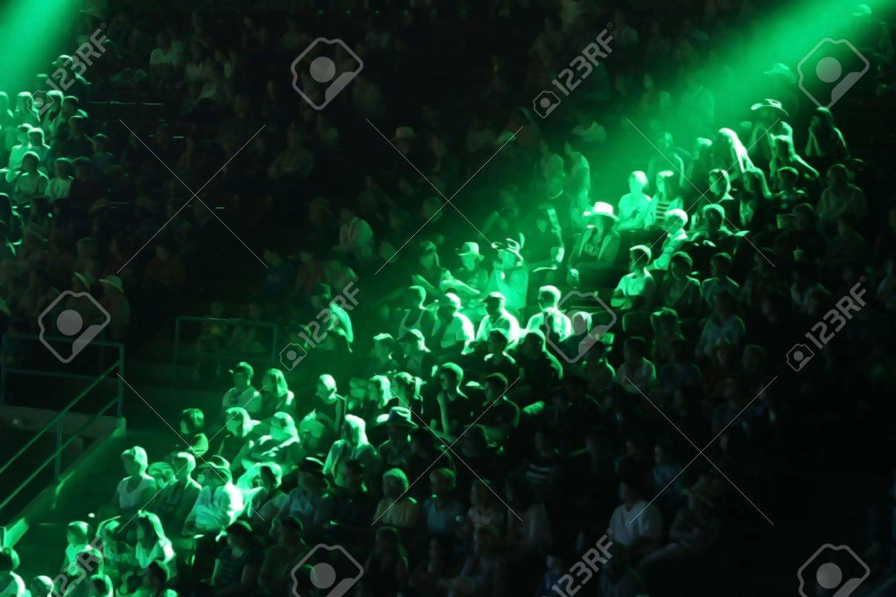 Unrecognizable audience of about 200 people in stadium seating - 7910564