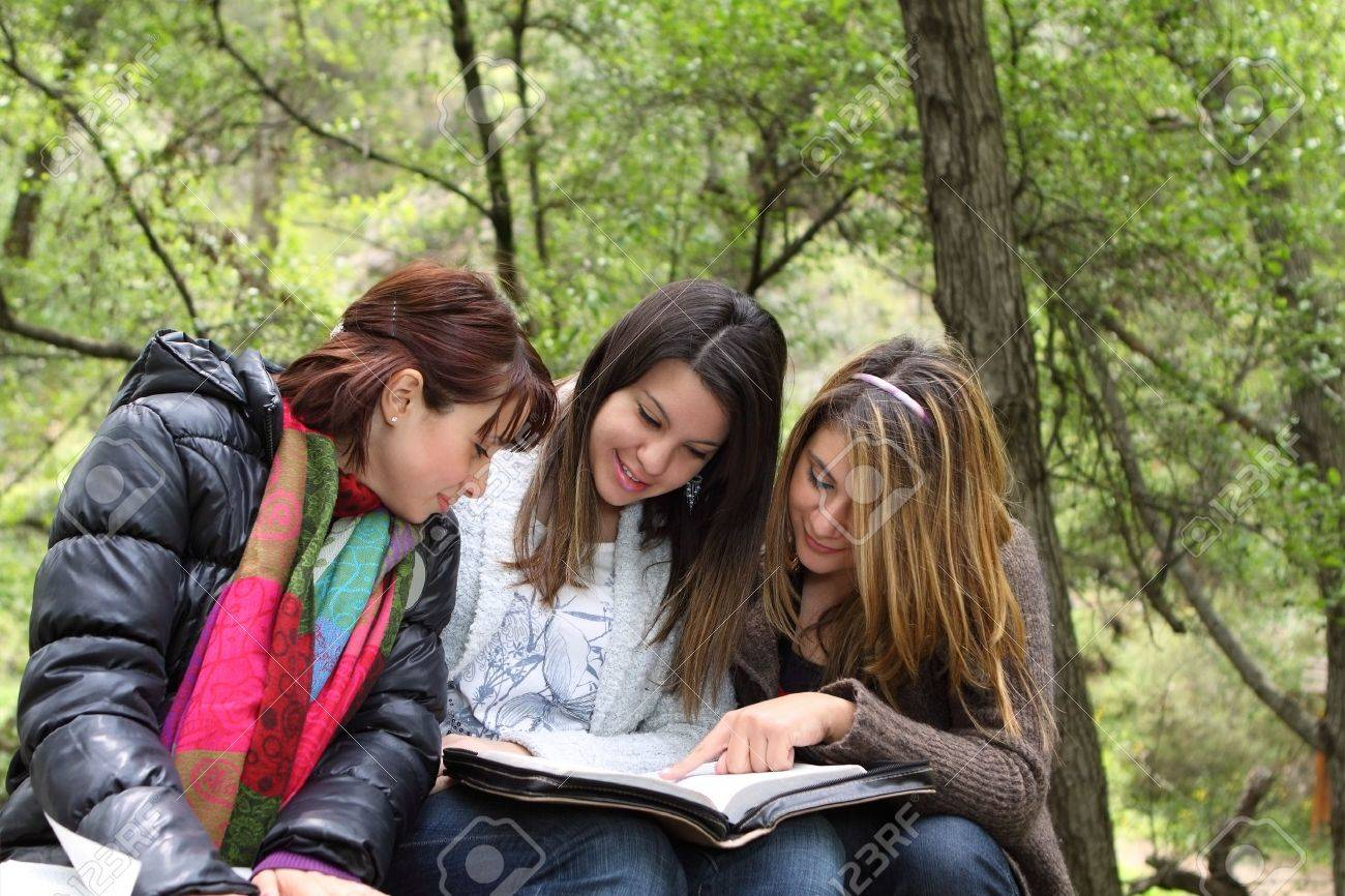 Three girls sitting in forest reading together - 9540383