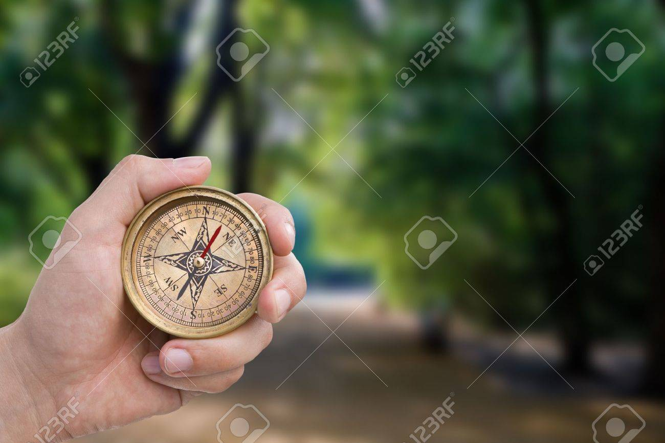 Male hand holding old compass. - 11180904