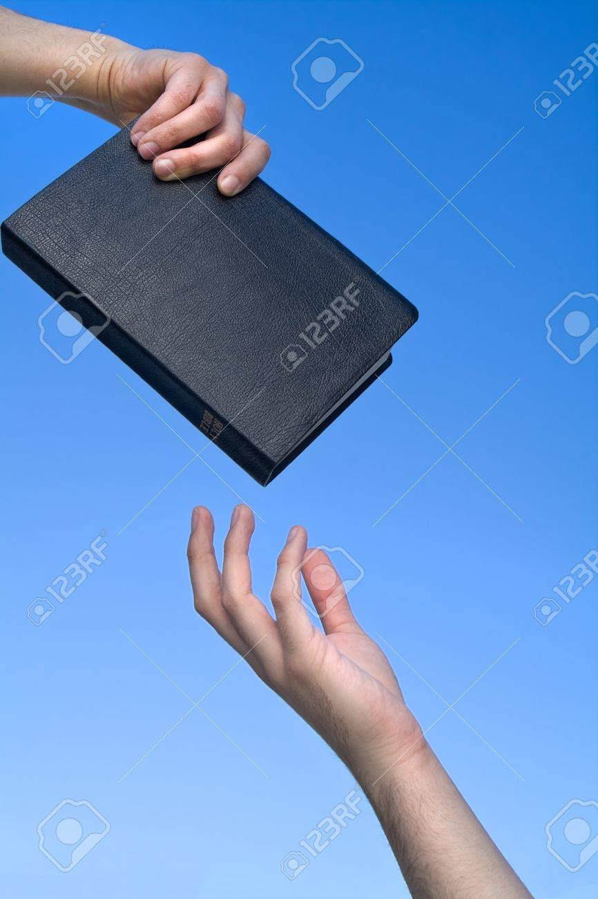 Hand giving the Bible to another person over blue sky - 12915838