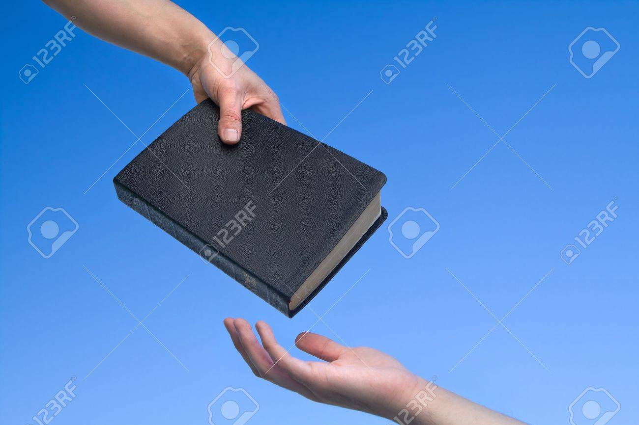 Hand giving the Bible to another person over blue sky - 12915842