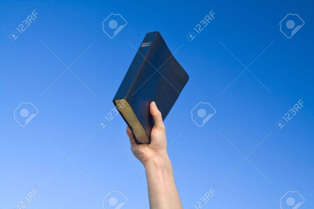 Hand holding Bible over blue sky - 12915832