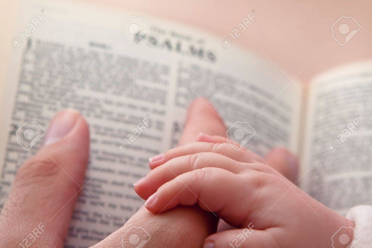 Baby holding father s finger as he points to Psalms verse - 18384238