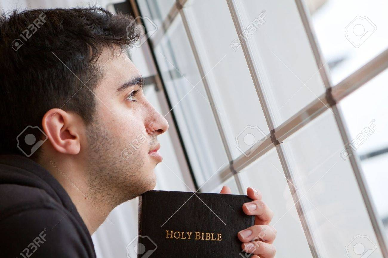Young man looking outside with Bible in hand - 18600528