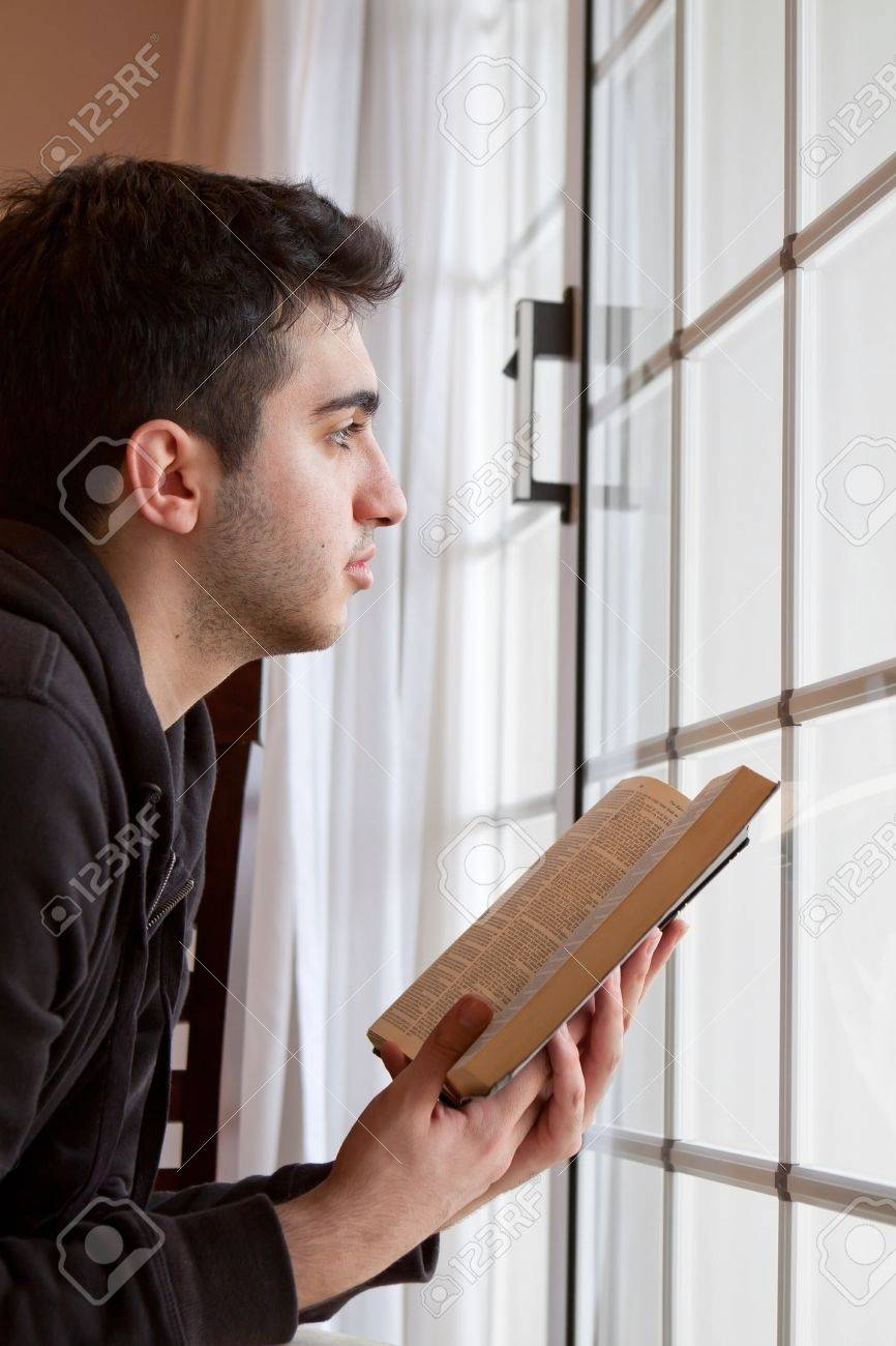 Young man looking outside with open Bible in hand Stock Photo - 18600526