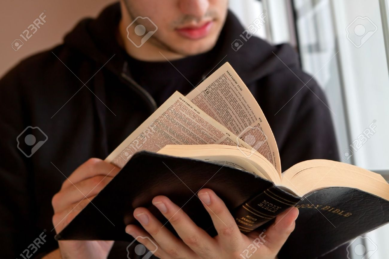 Young man reading the Bible - 18600523