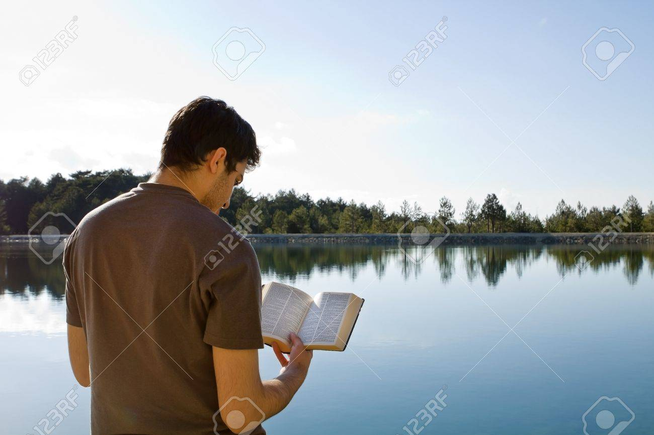 Young man in front of lake reading the Bible - 19454796