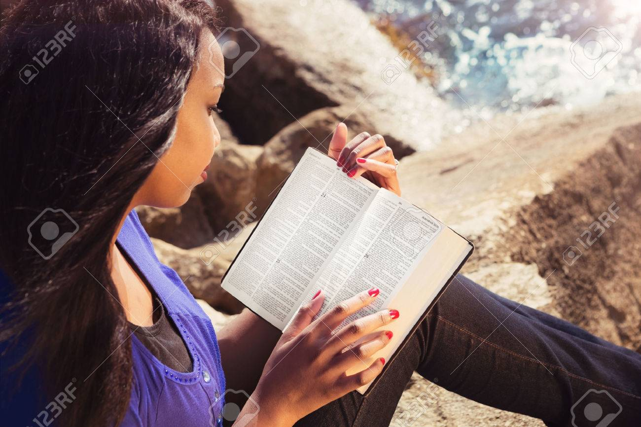 Young girl reading her Bible by the sea - 28098246