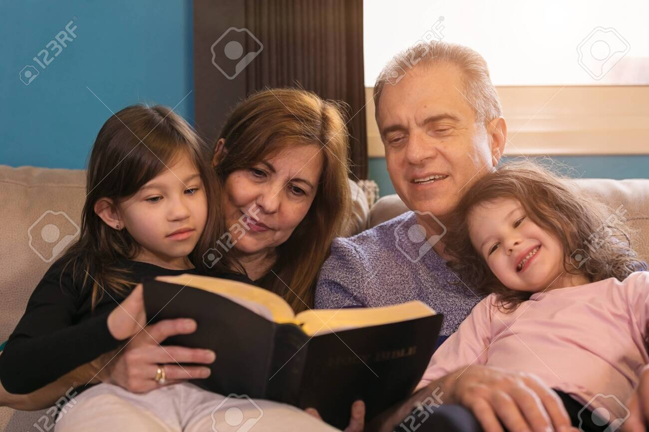 Grandparents teaching grandchildren about the Holy Bible - 146519278