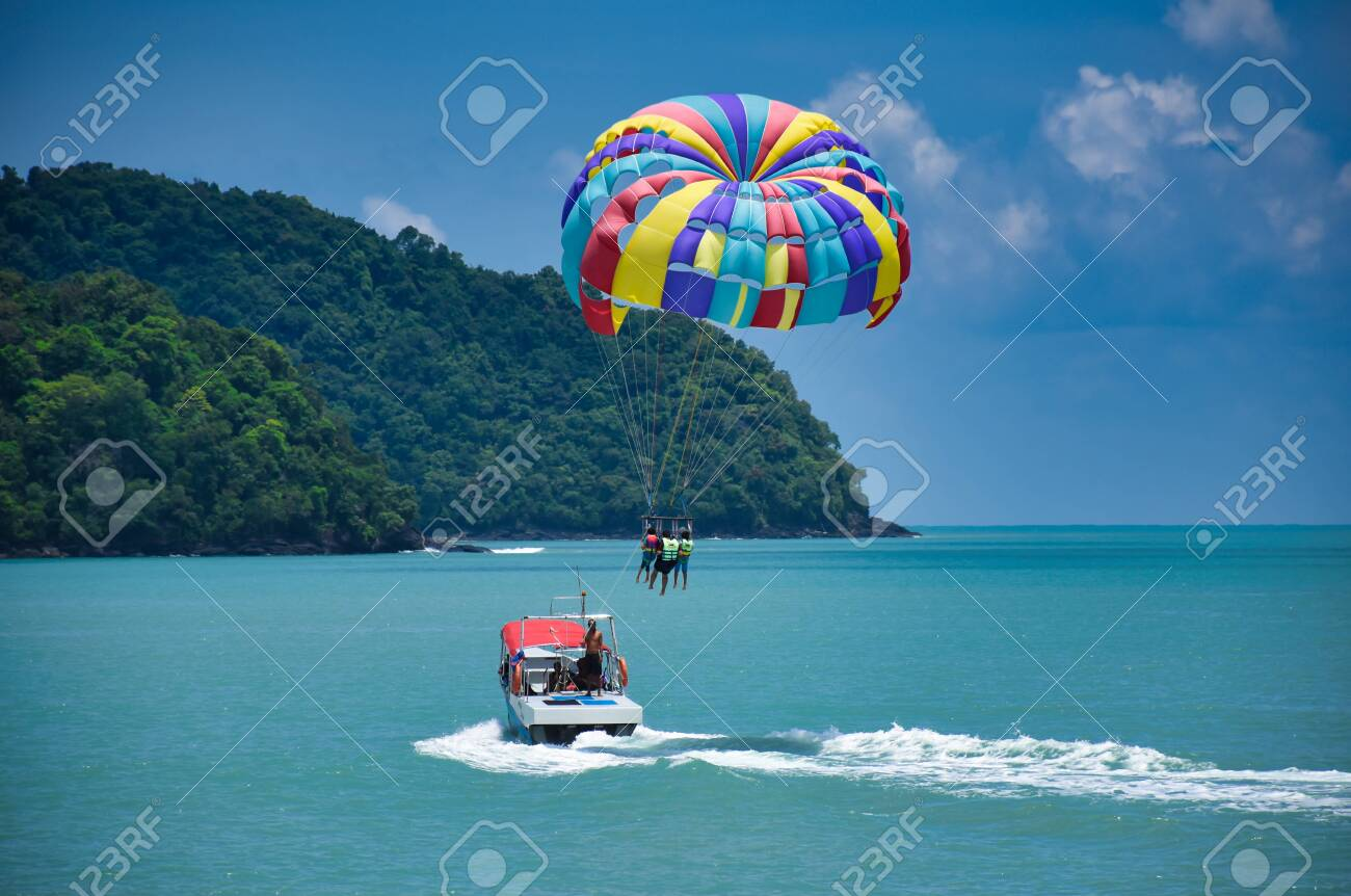 Parasailing on the waves of the azure Andaman sea under the blue sky near the shores of the sandy beautiful exotic and stunning Cenang beach in Langkawi island, in Malaysia. - 134445167