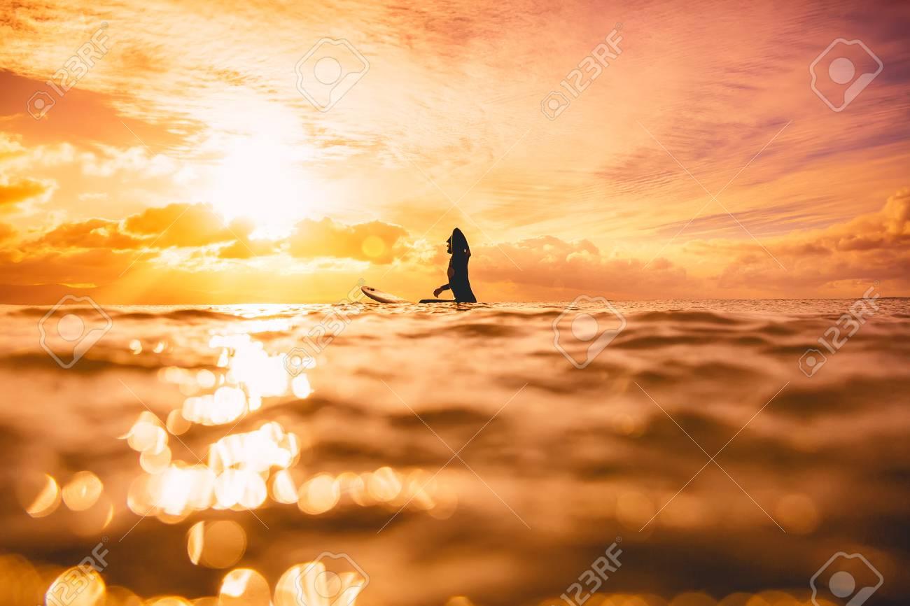 夕日や日の出の海で女性はスポーティなサーフィン 冬の海での