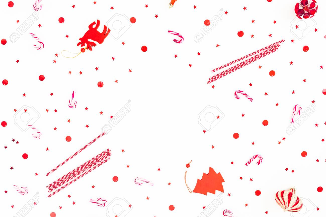 Frame of Christmas decoration, candy canes and red confetti on