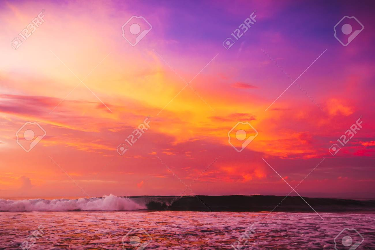 waves in the ocean at bright pink sunset or sunrise ocean with
