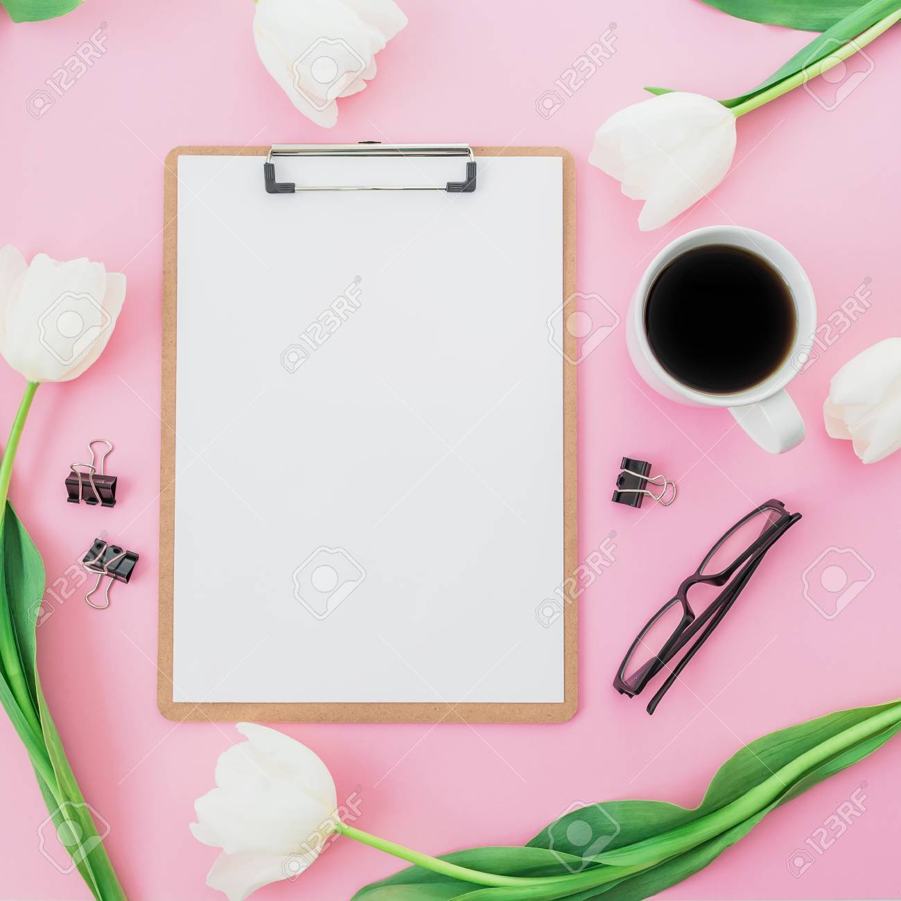 tulips flowers with mug of coffee clipboard and glasses on pink