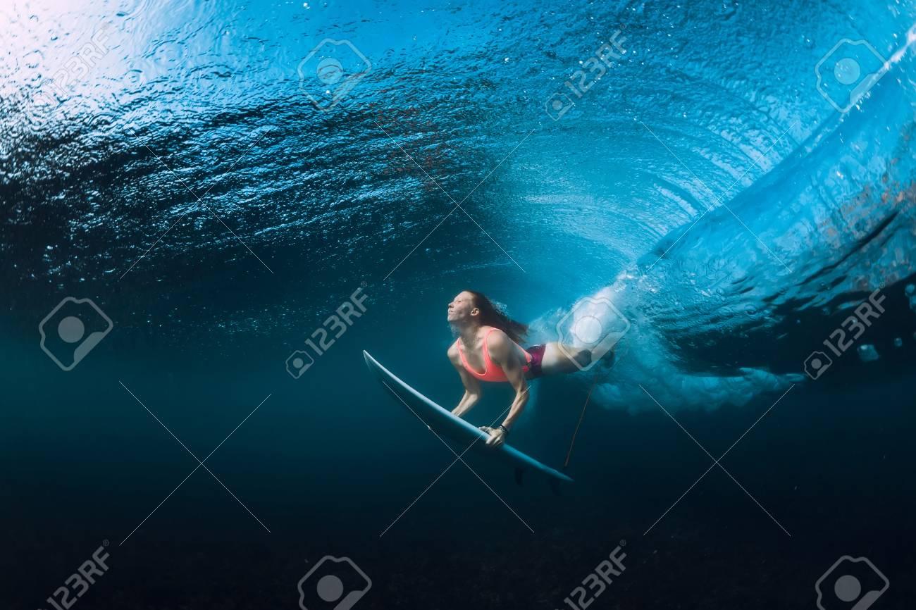 Surfer woman dive underwater with under barrel wave. - 115868490