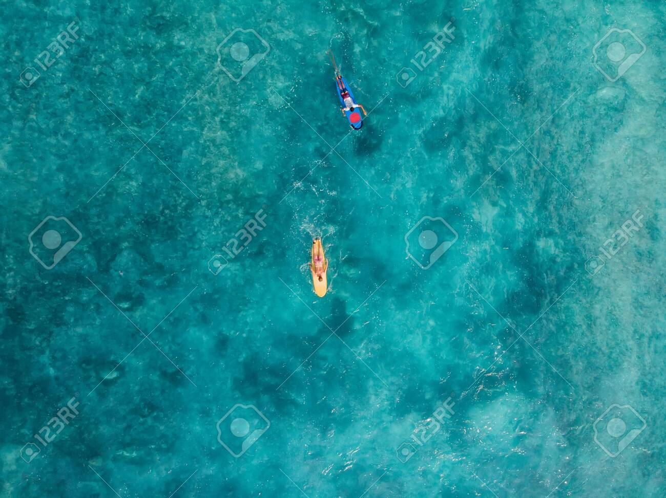 Aerial view of surfers on surfboard in blue ocean. Top view - 144596889
