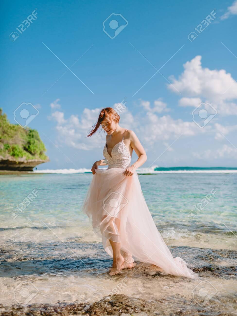 July 5, 2020. Bali, Indonesia. Wedding day of red head bride in wedding dress at tropical beach. Happy wedding in tropical Bali - 154116553
