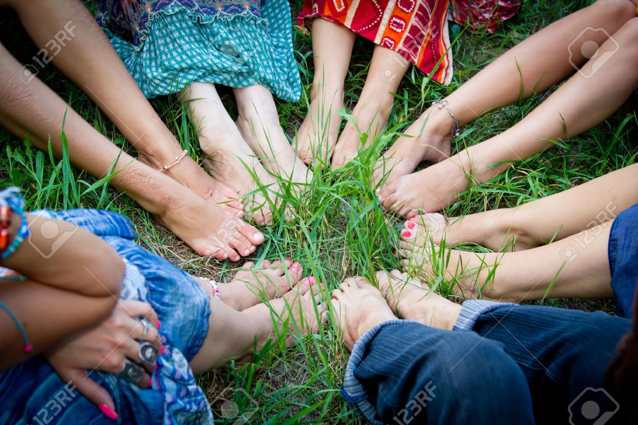 bare feet of group of young girls in a circle on a green grass stock