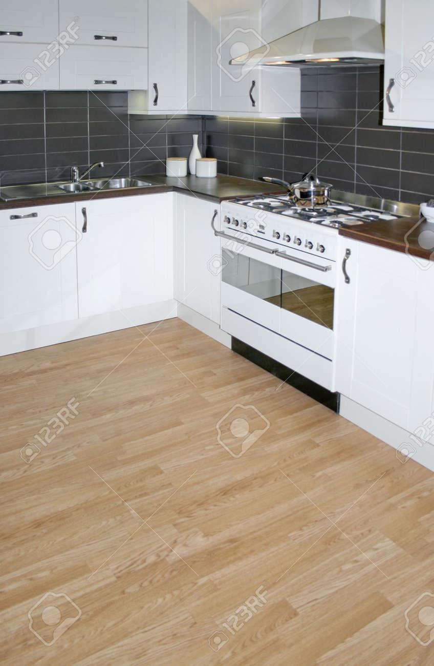 Moderne Witte Keuken Met Bruine Houten Vloeren Royalty-Vrije Foto ...