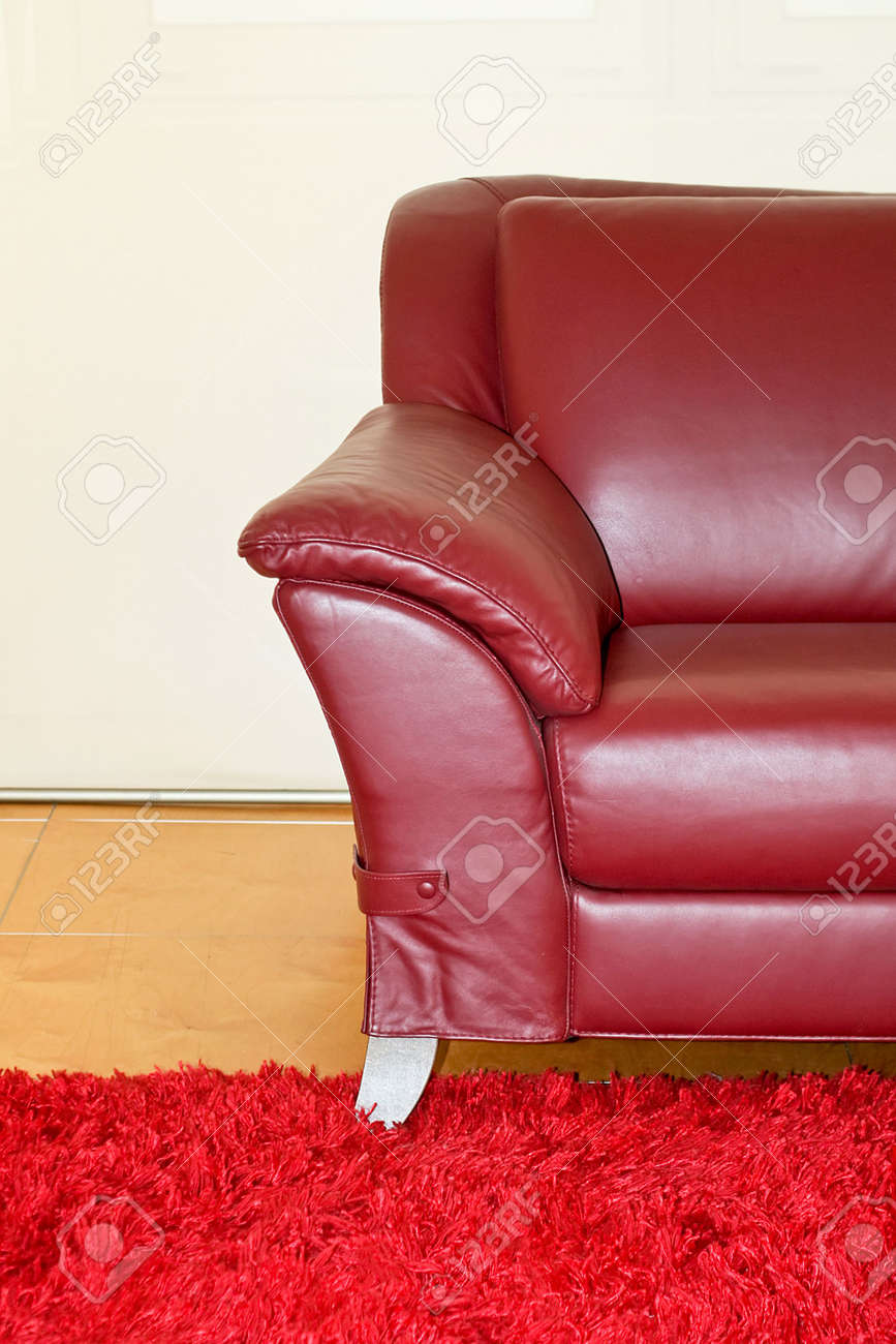 Part of dark red leather sofa with armrest
