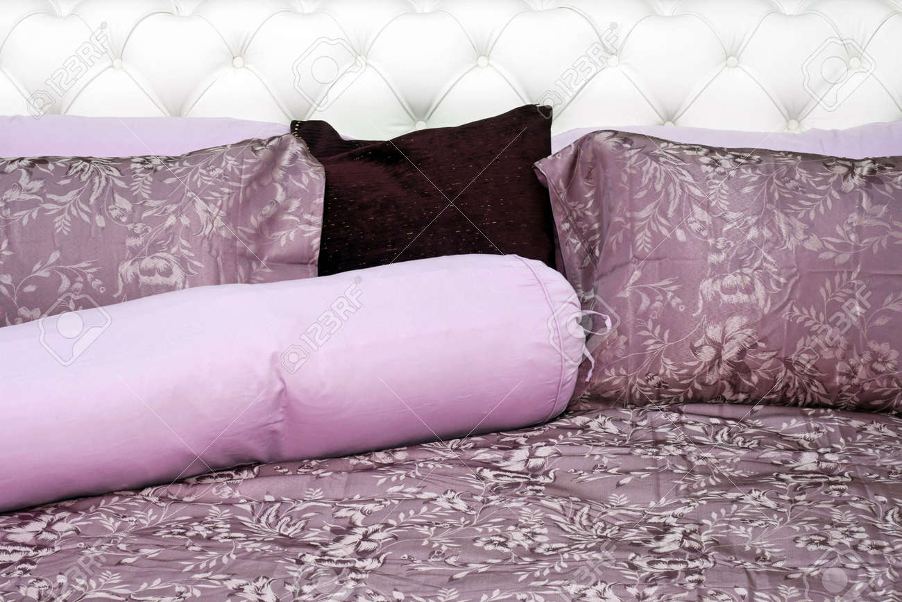 Purple bedding sheets with pillows on leather bed Stock Photo - 2409275