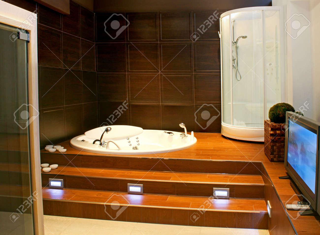 fett aus holz badezimmer mit großen lcd-fernseher lizenzfreie