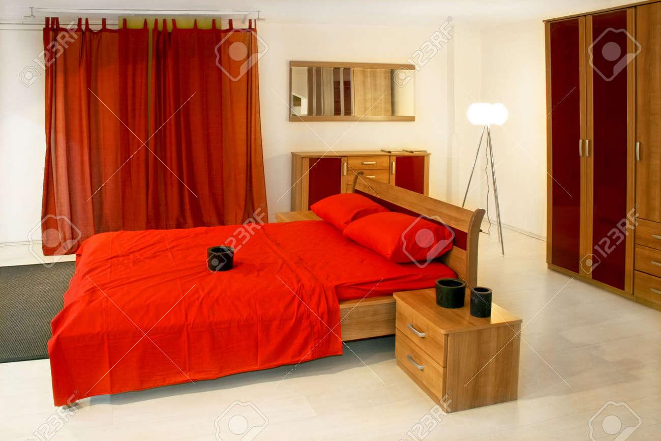Chambre à coucher avec des meubles en bois rouge et la literie ...