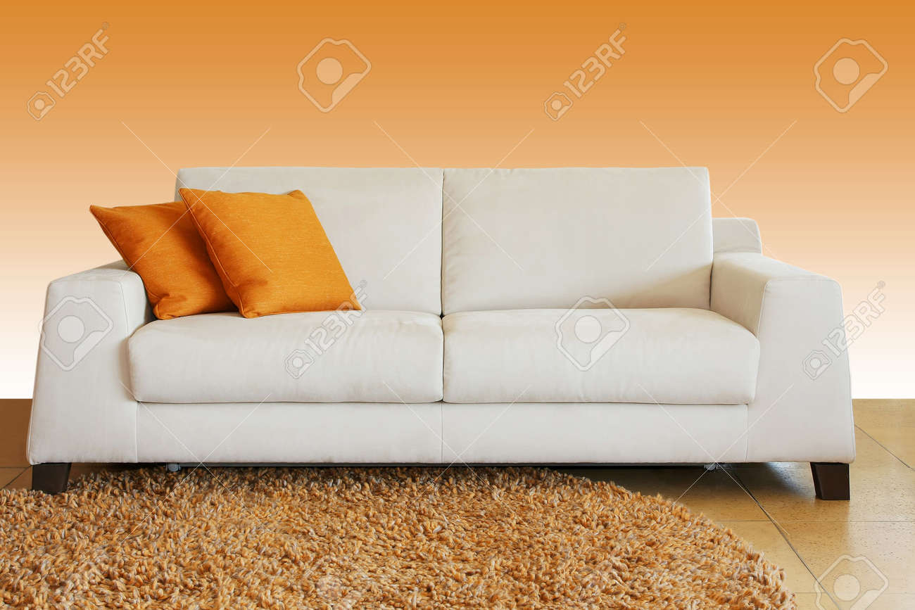 White leather sofa with two orange pillows