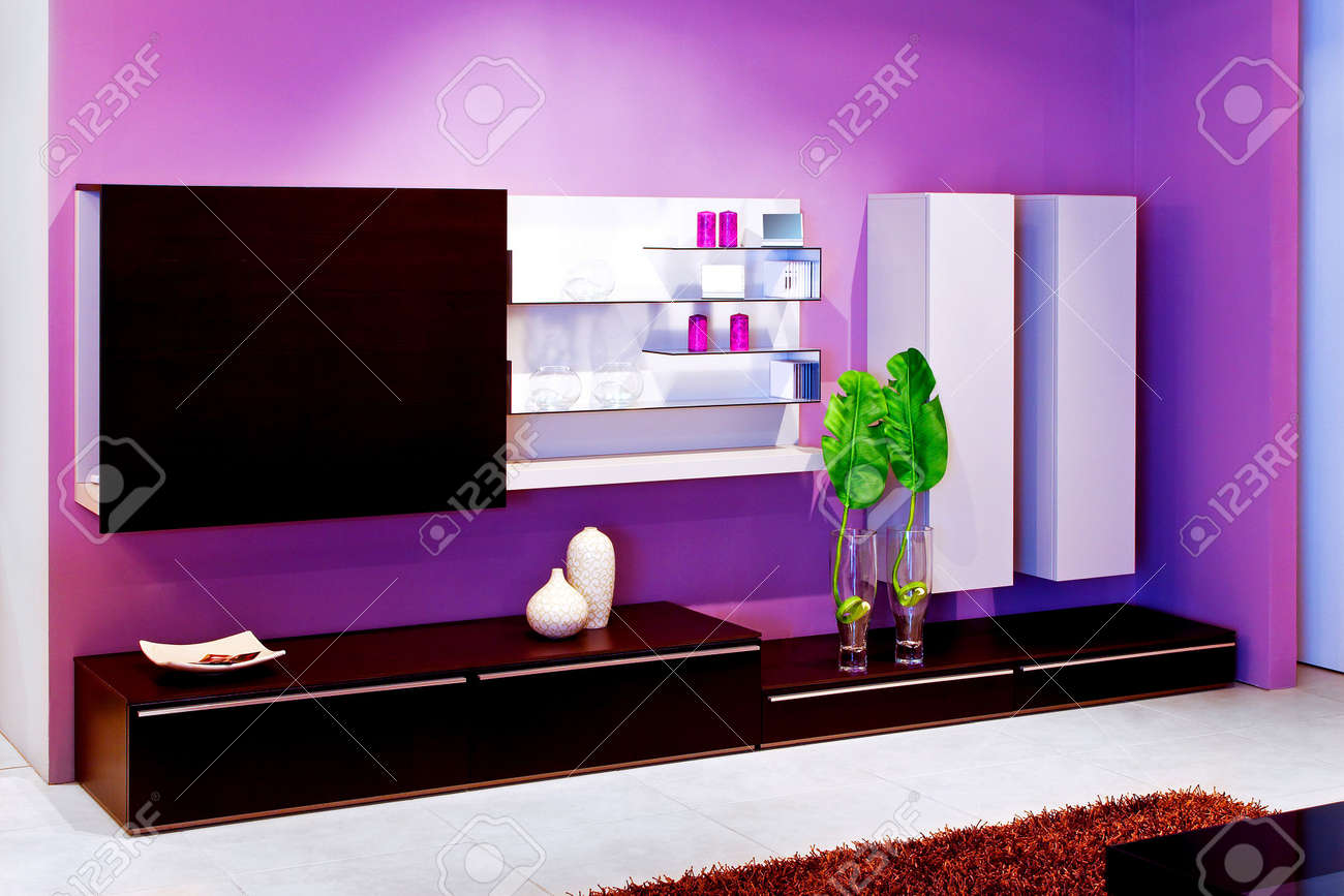 Shelf In Living Room With Purple Walls Stock Photo