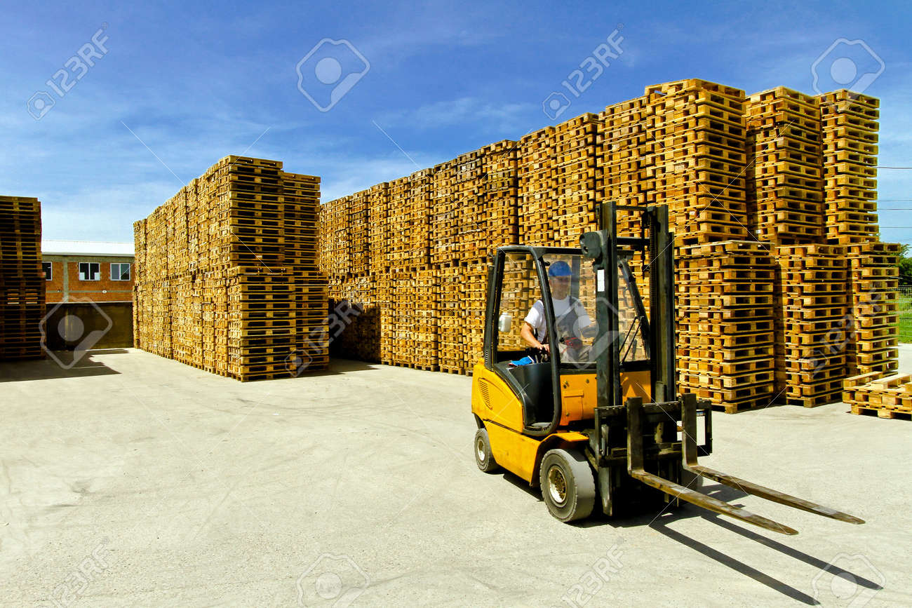 Man operating forklift inside of pallet warehouse Stock Photo - 8575174