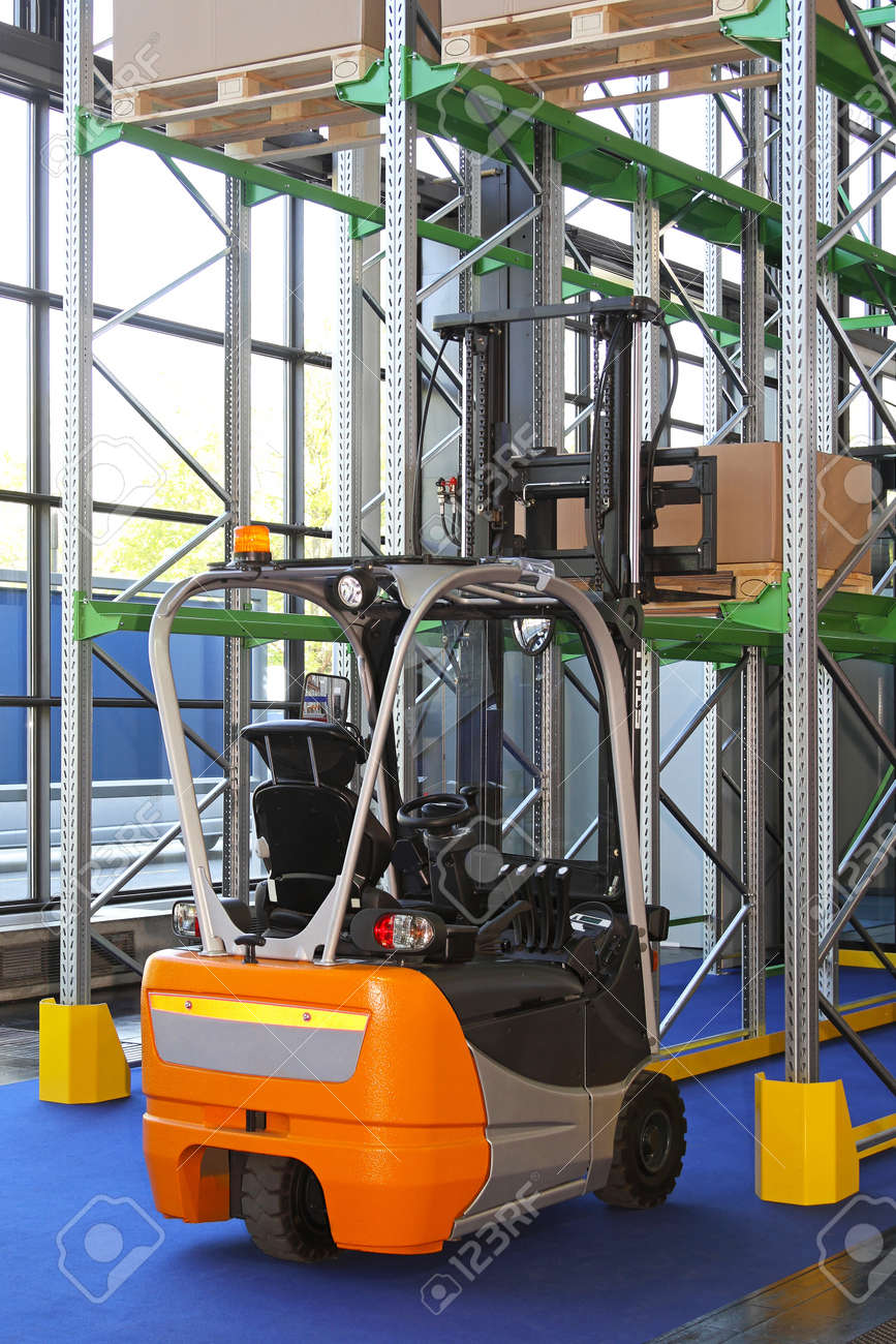 Small electric forklift truck in distribution warehouse