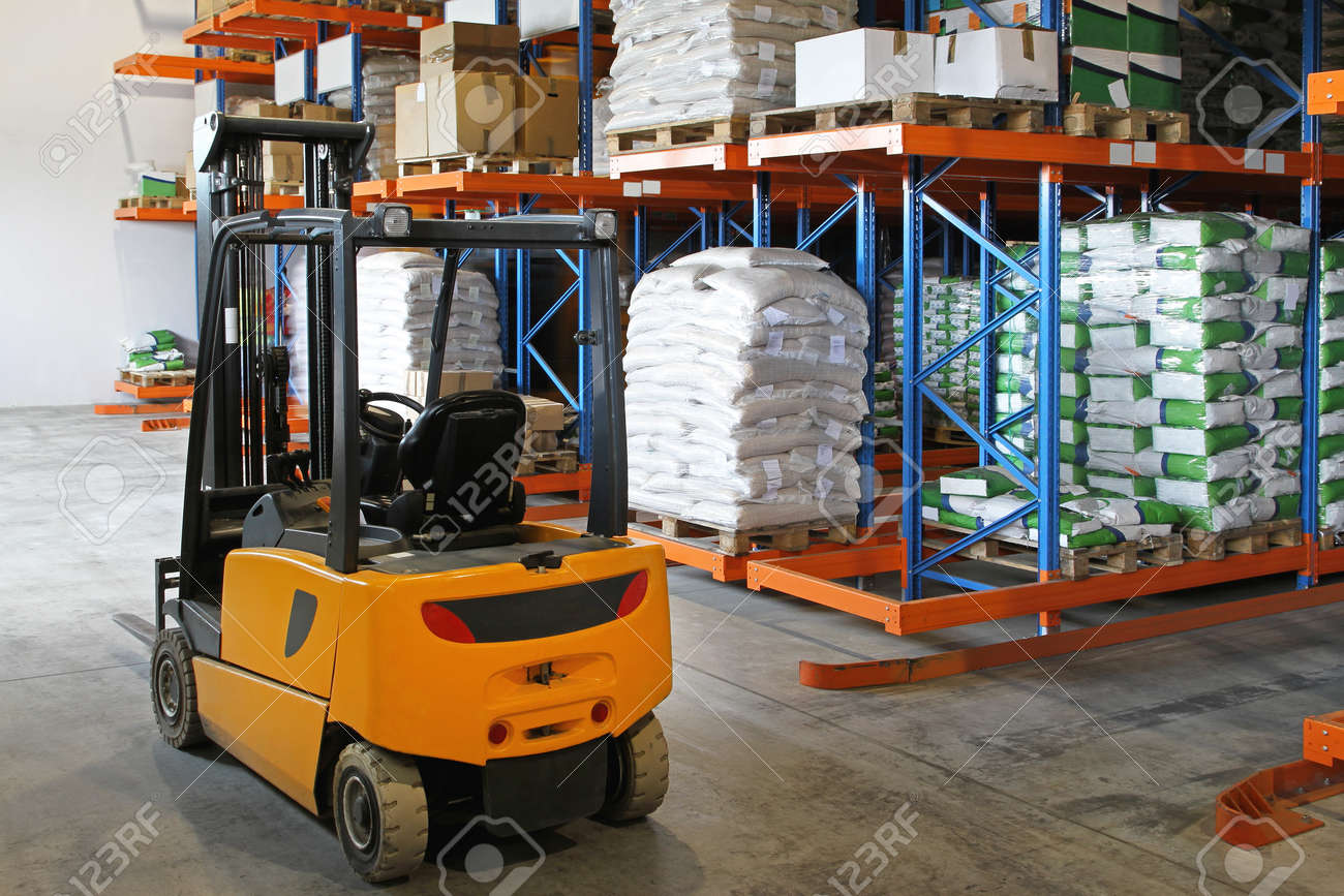 Yellow forklift in distribution warehouse with sacks Stock Photo - 18352965