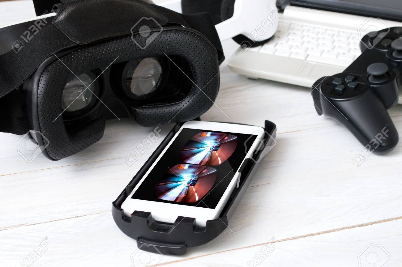 Smartphone laying on desk and prepared to play with VR googles. Game on screen was created in graphic program - 64093833