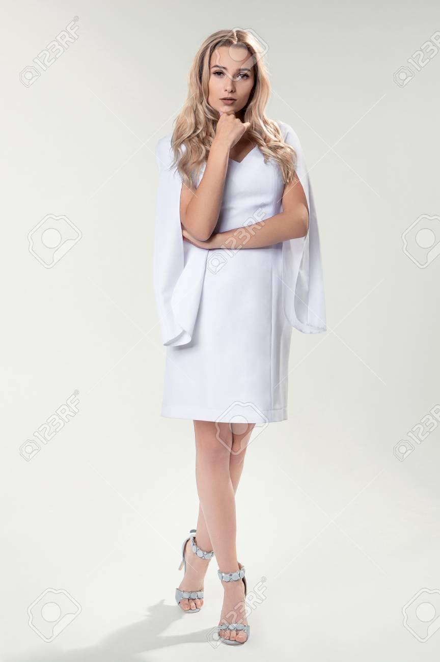 73980525bd2 Jeune Blonde En Robe élégante Blanche Sur Fond Blanc Banque D Images ...