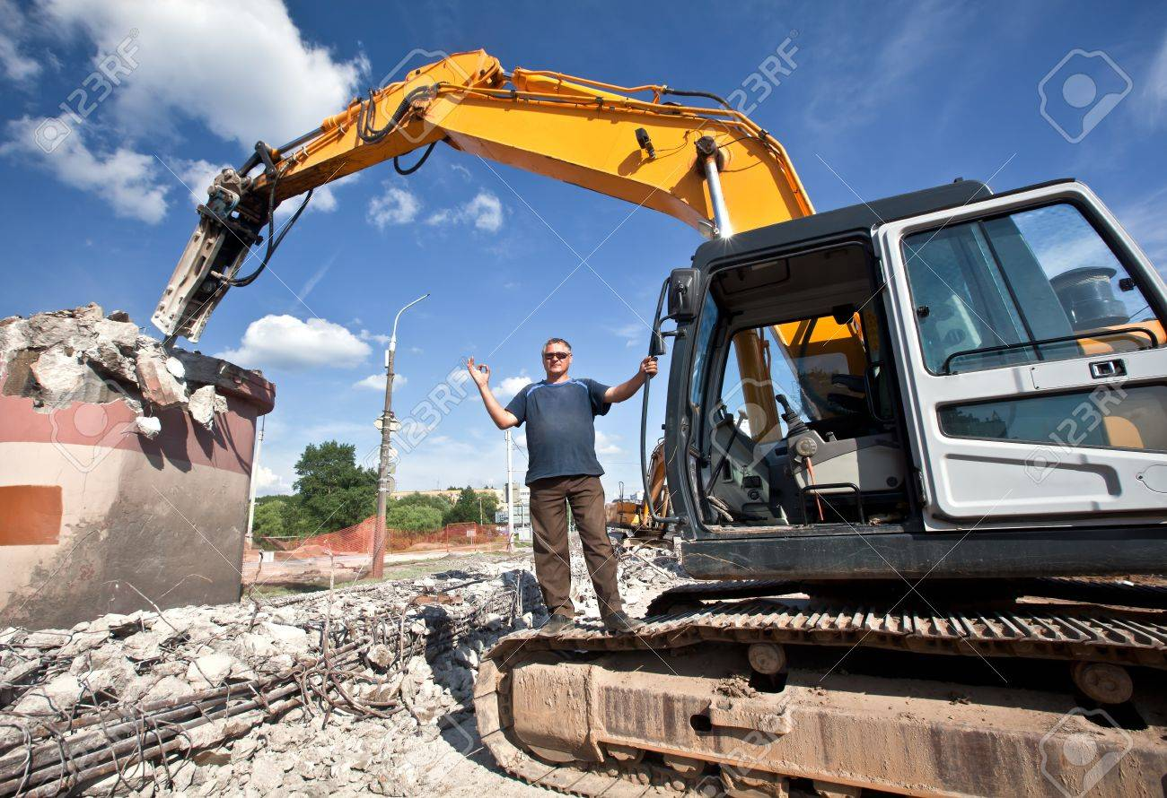 Сonstructor with hydraulic hammer destroys reinforced concrete structures Stock Photo - 10669411