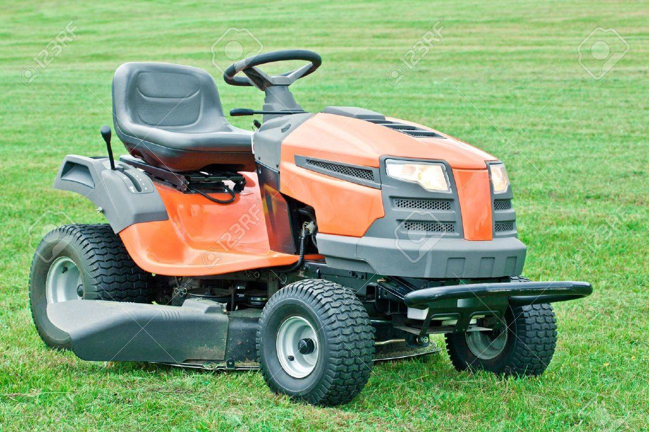 Lawn mower with the lights on against on green grass background - 12538077