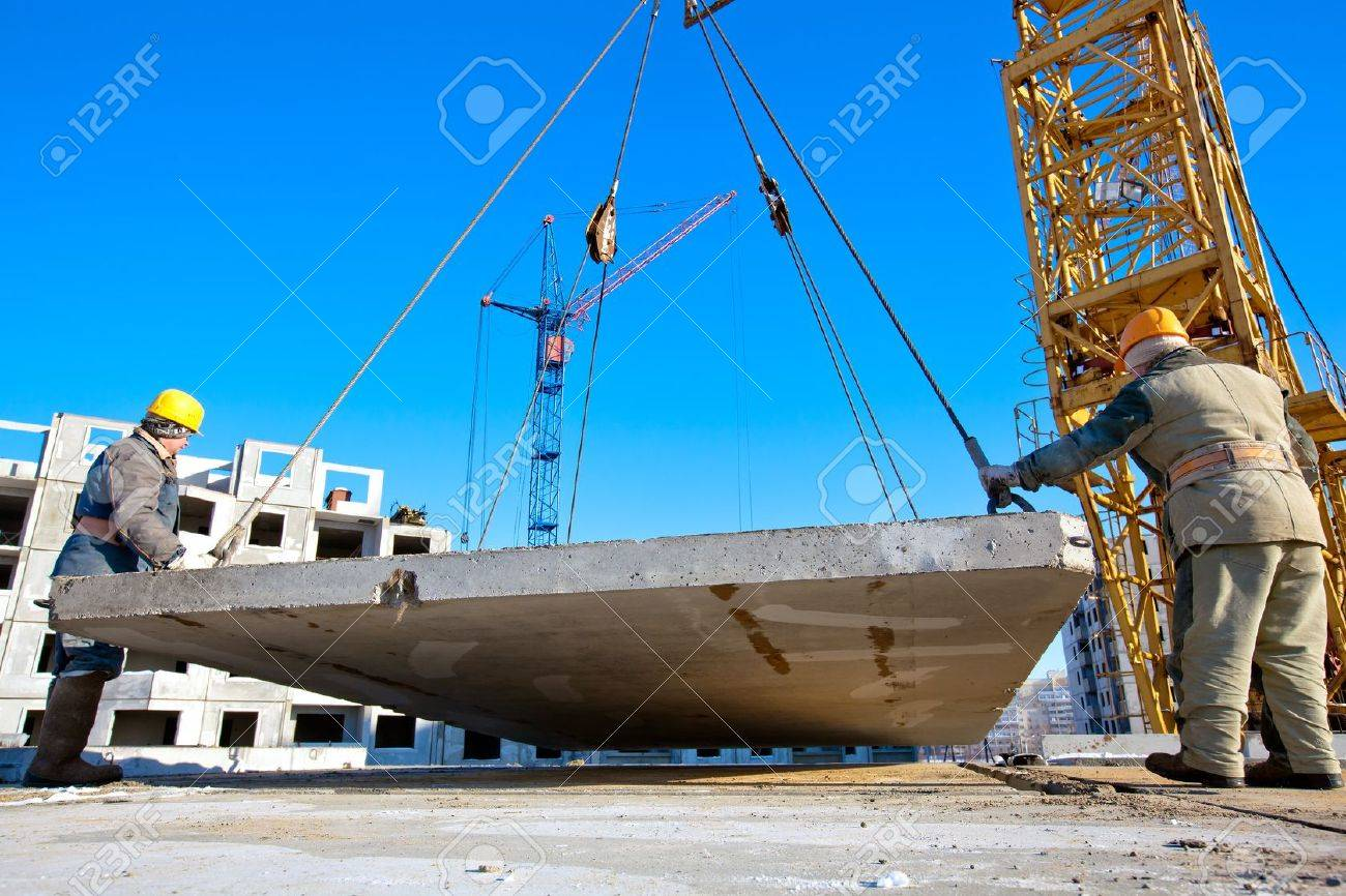 Two industrial workers with hardhats and uniform unloading concrete plate from crane at construction site during the erection of multistory building Stock Photo - 12538091