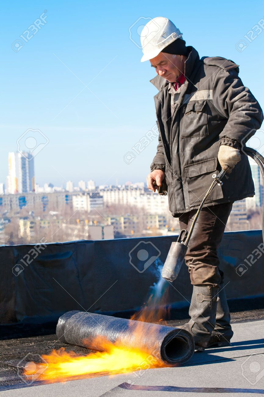 Roofer man worker in helmet installing a roll of roofing felt by means of gas blowpipe torch Stock Photo - 15376139