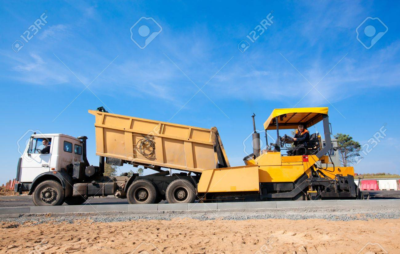 Tipper unloading fresh asphalt from body into tracked paver during pavements construction works Stock Photo - 18569144