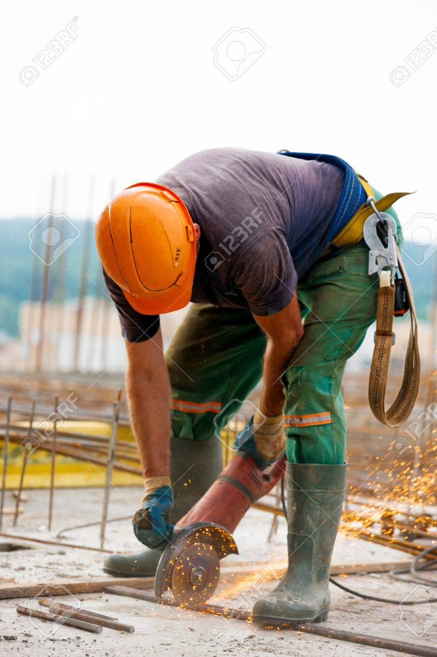 Builder worker sawing metal at construction site - 21699047