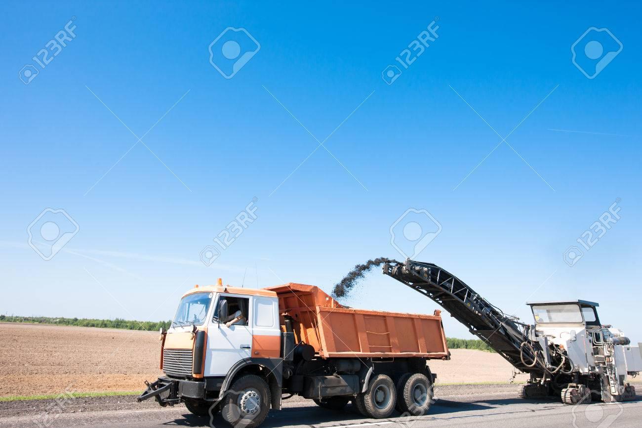 milling machine loading crushing asphalt into dump truck during
